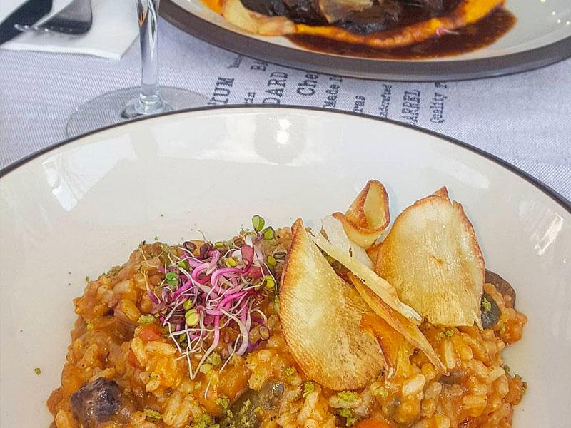 Risotto Mar y Montaña con salsa americana, langostinos, hongos y chips de boniato.